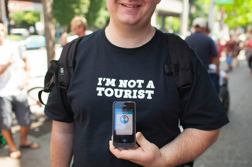 Man with t-shirt that says I am not a tourist with an iphone infront of him
