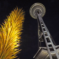 The Chihuly Garden and Glass exhibit at the Seattle Centre is illuminated at night with the Iconic Space Needle streching into the sky in the background.