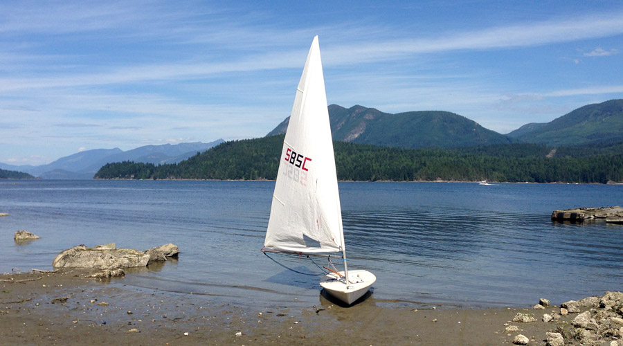 Snake Bay Sailing Club Laser with a reefed sail on the shores of Porpoise Bay in Sechelt, BC.