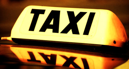 The warm yellow glow of a taxi cab sign look welcoming but rarely is.