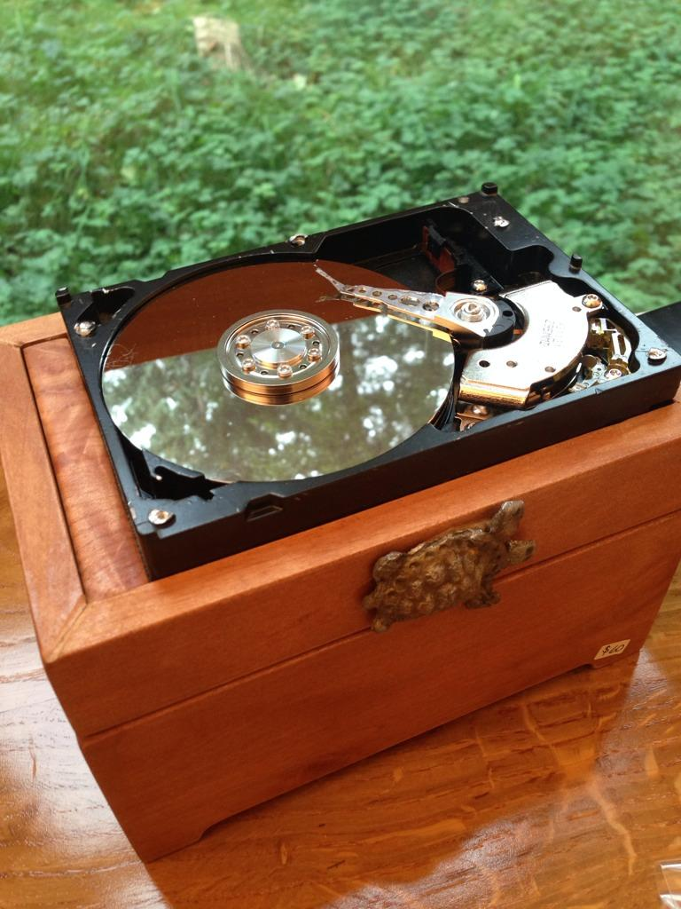 Bits and Bytes A wooden box with an old hard drive placed on top. Artist Peter Sugars
