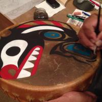 Tony Paul painting a killer whale on a drum at the Sechelt Nation Long House