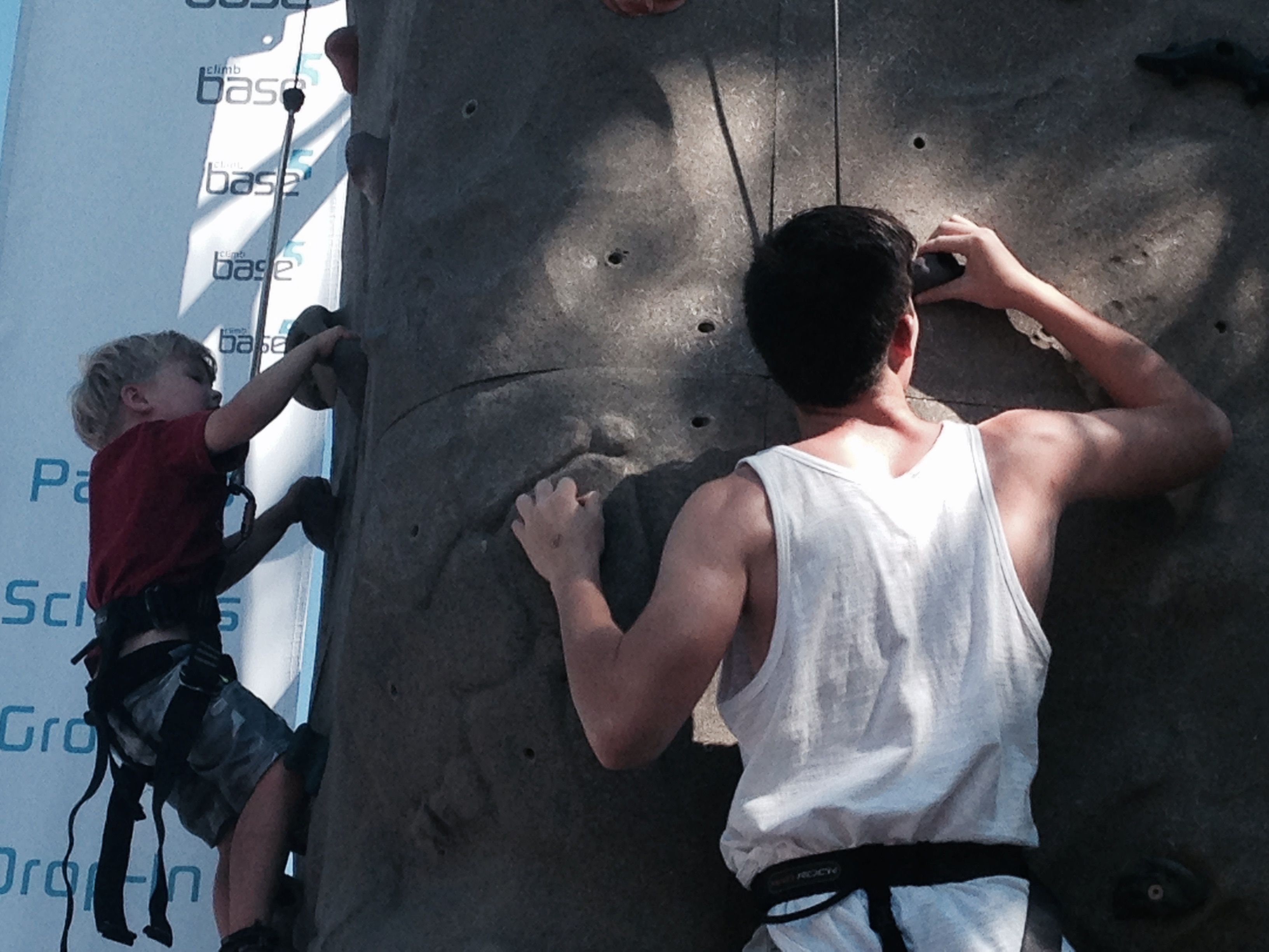 A boy and man scale a climbing wall in the sun.